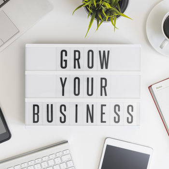 grow your business sign on desk with computer, tablet, phone, notepad and coffee