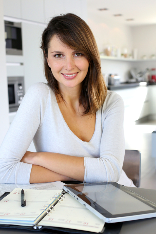young woman sitting at a kitchen table with planner and tablet